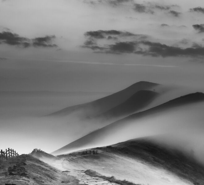 A mono view of mist rolling from the Hope Valley to the Vale of Edale