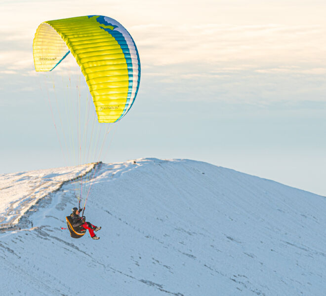 Paraglider over snowy Mam Tor
